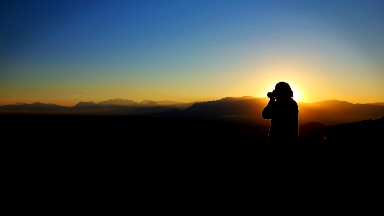 Photographer taking photo in the mountains during the sunset