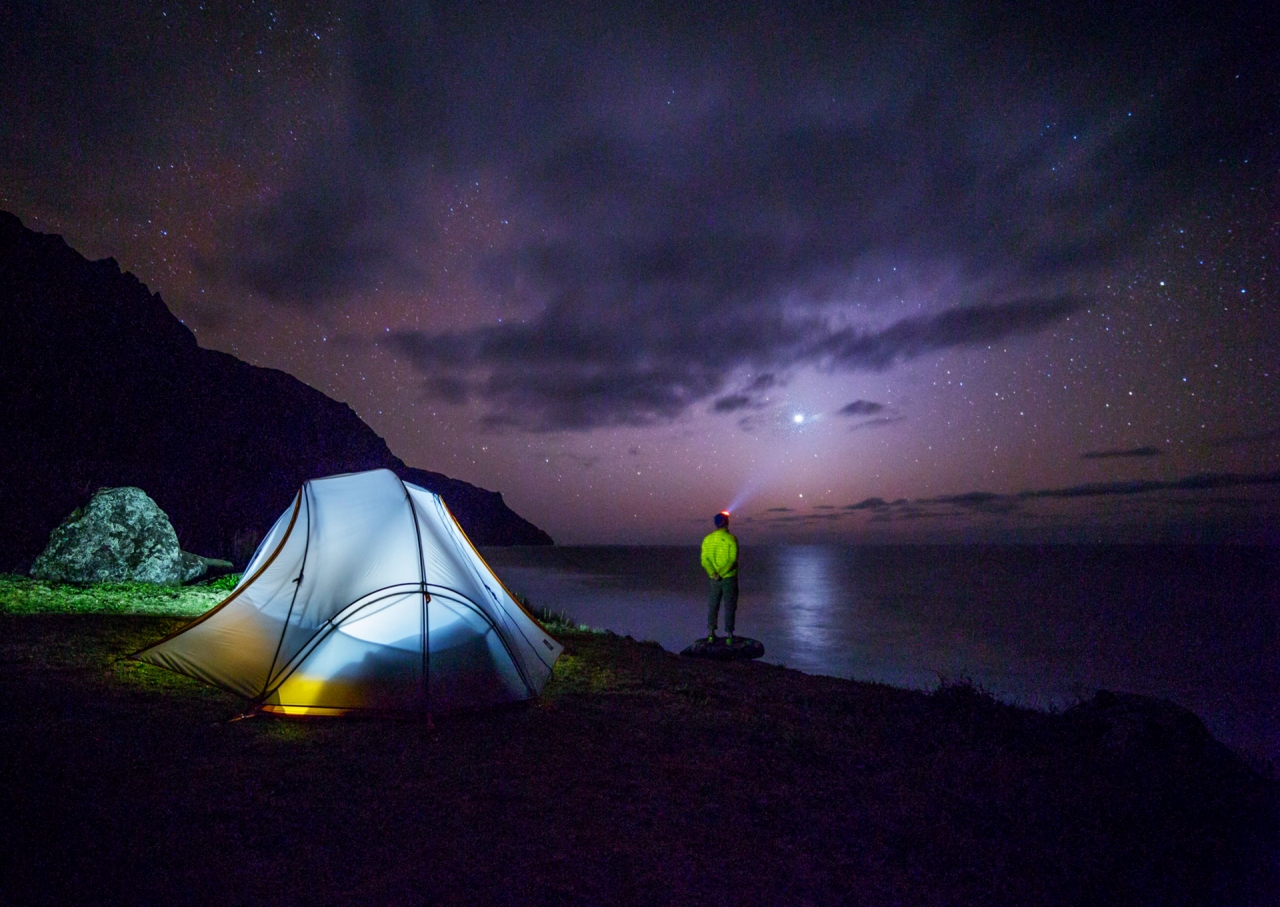 Traveler camping wild near the sea during the night with stars
