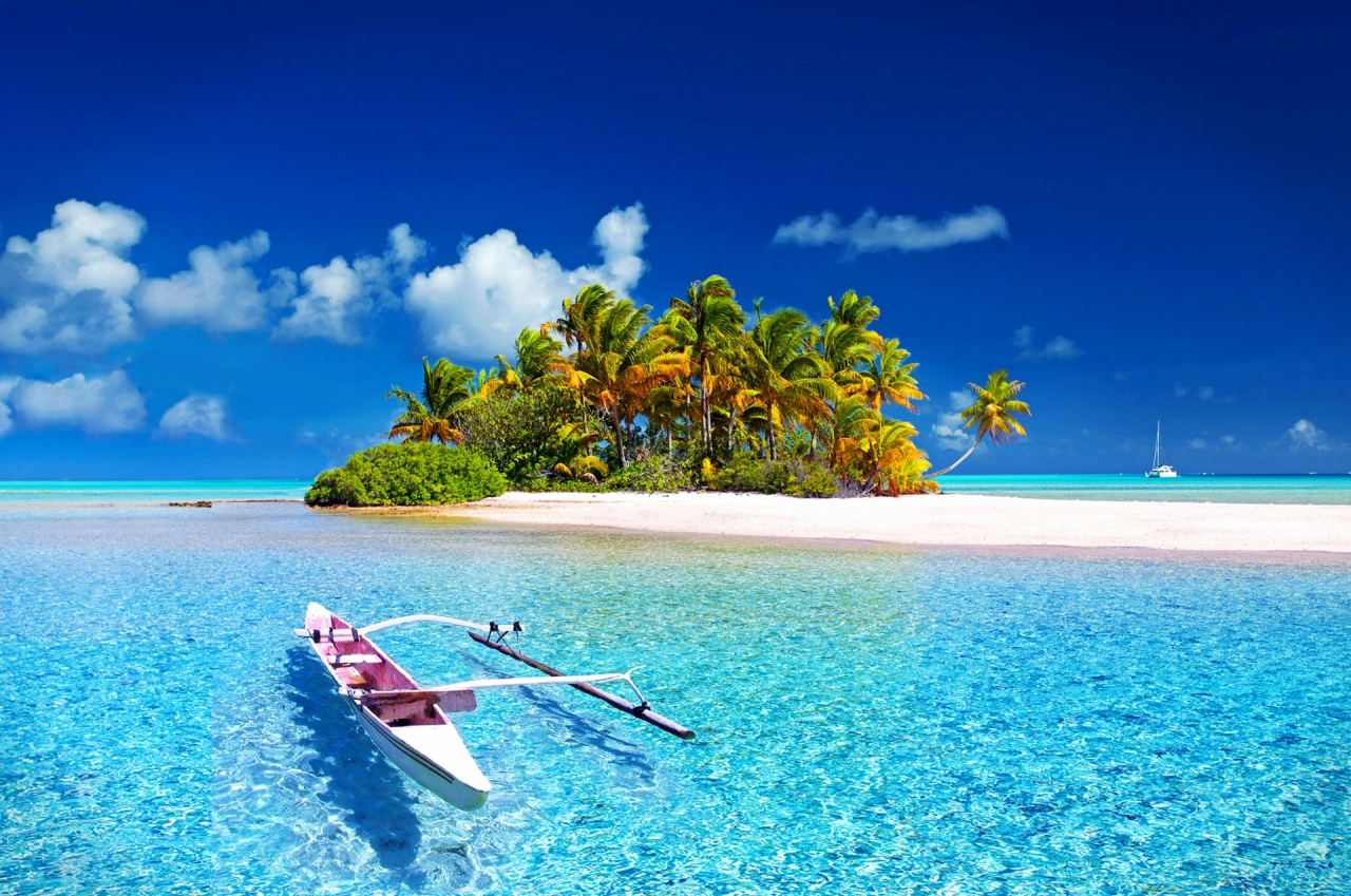 Beautiful island with a sandy beach and boat, blue water