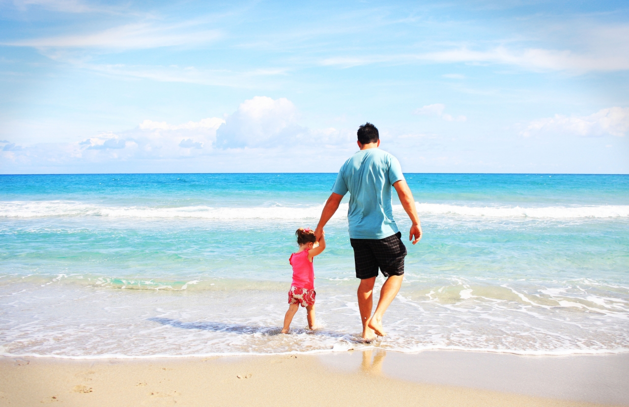 Father with daughter (family) on the sandy beach during vacation