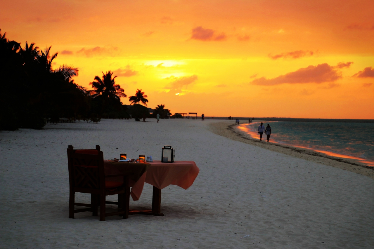 Restaurant table with dinner on the beach during the sunset on Maldives