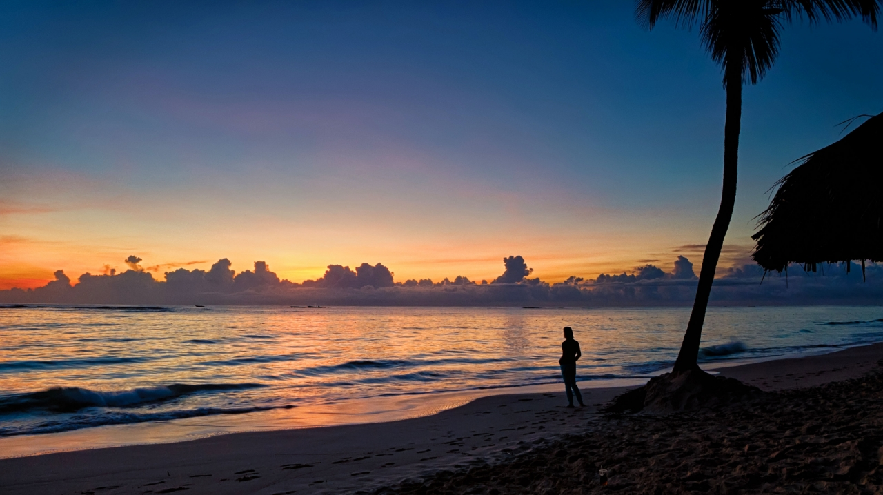 Young girl on the beach during the sunrise