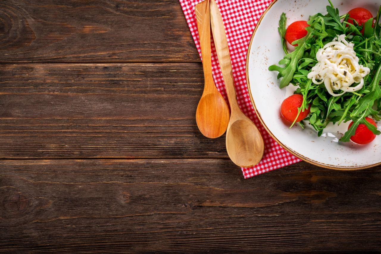 Italian salad on the wooden background in the kitchen