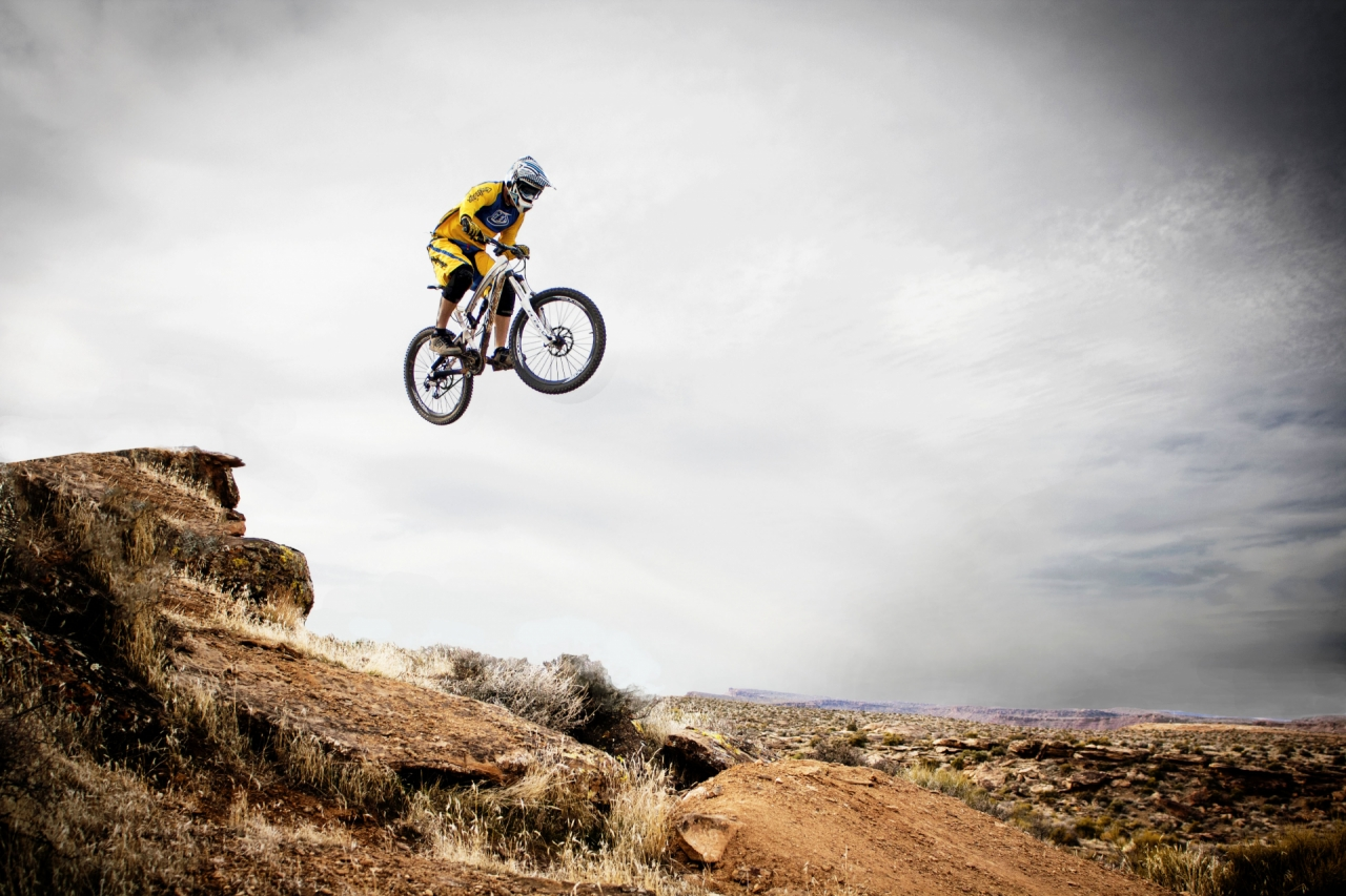 Man jumping and mountain biking in Utah