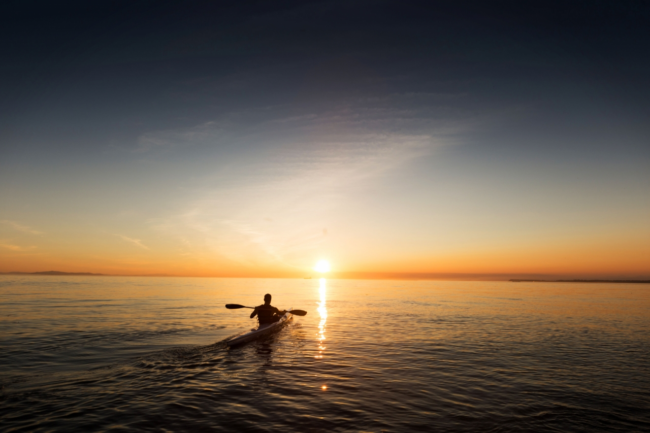 Man paddling in kayak and canoe on the ocean during the sunset