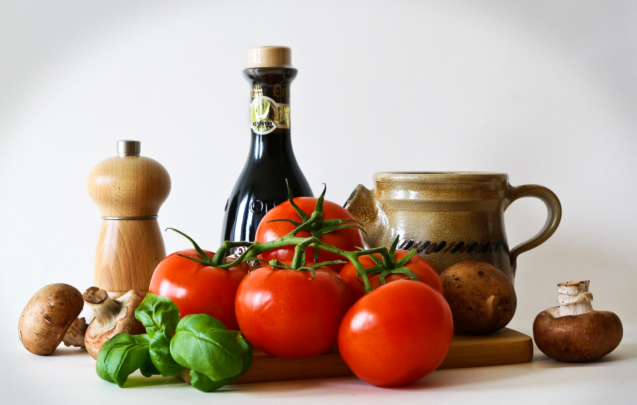 Tomatoes, mushrooms and olive oil on white background