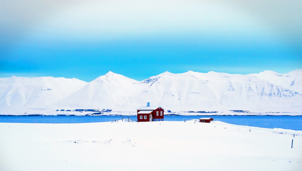 Red cottage in Iceland, winter and snowy mountains