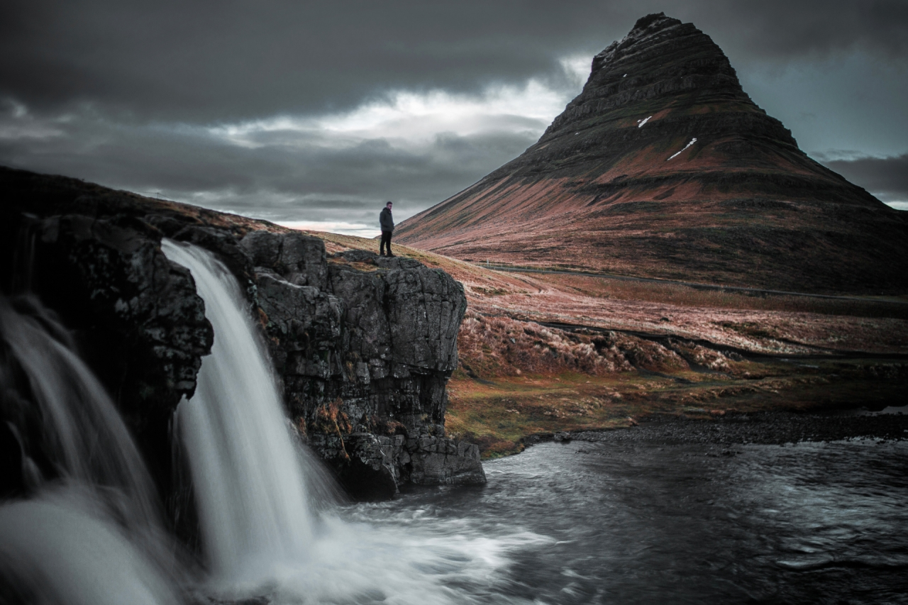 Traveler, mountain and waterfall in Iceland