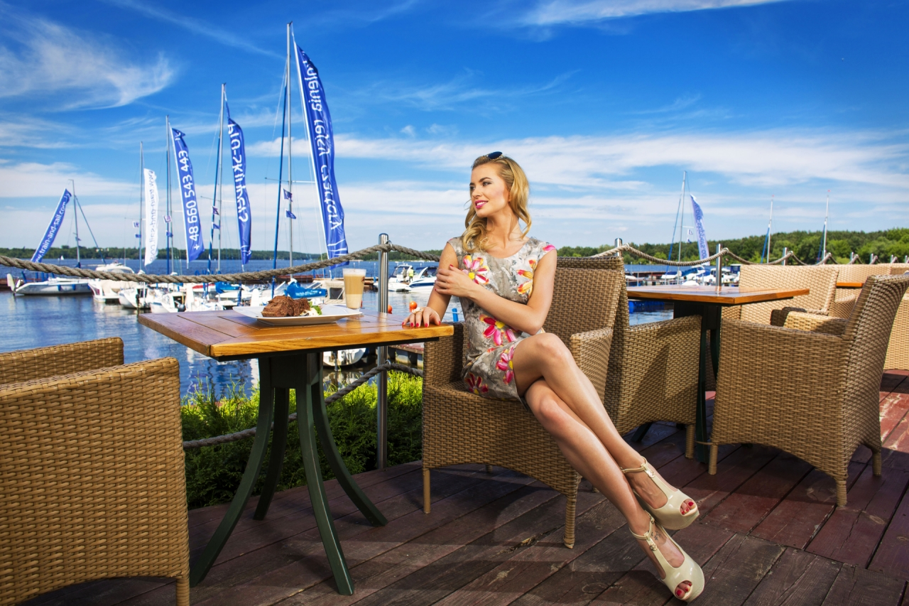 Woman sitting in restaurant near water, lake and boats