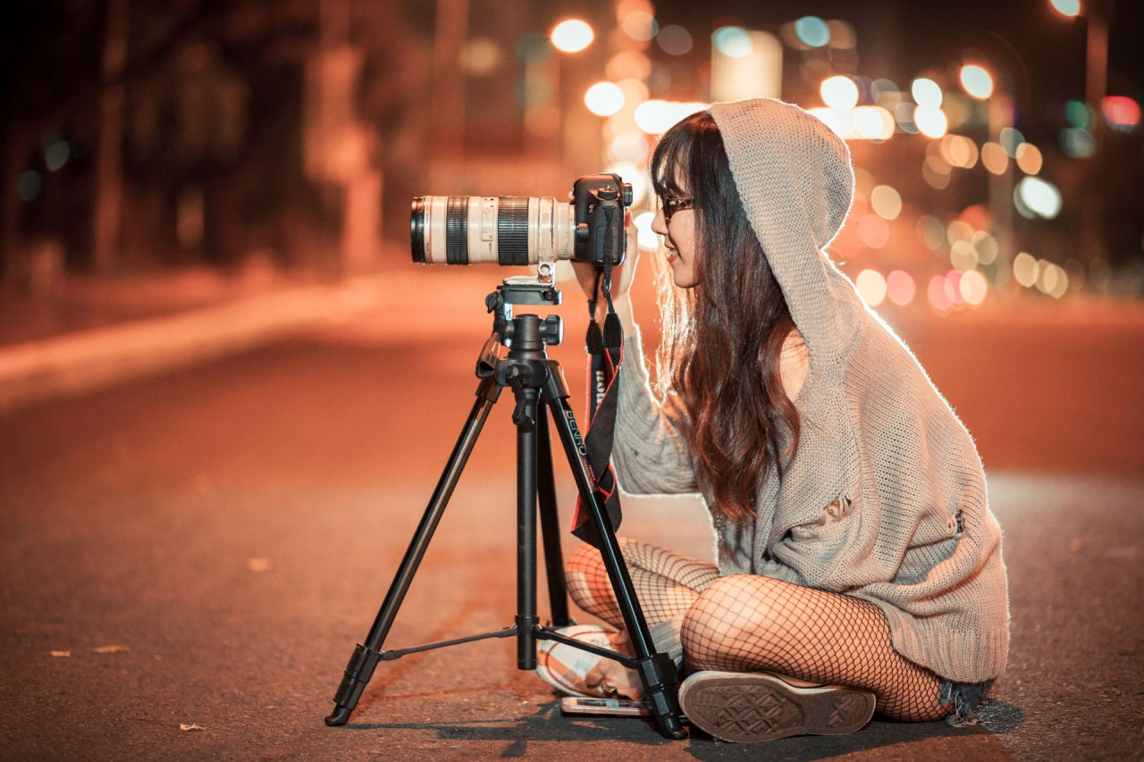 Girl photographer taking a picture outdoors during the night