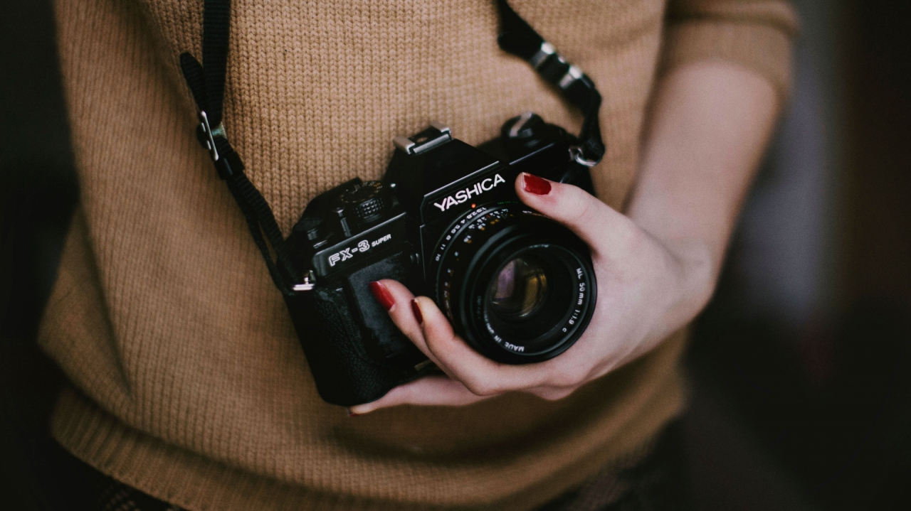 Photographer woman with retro Yashica camera in her hand