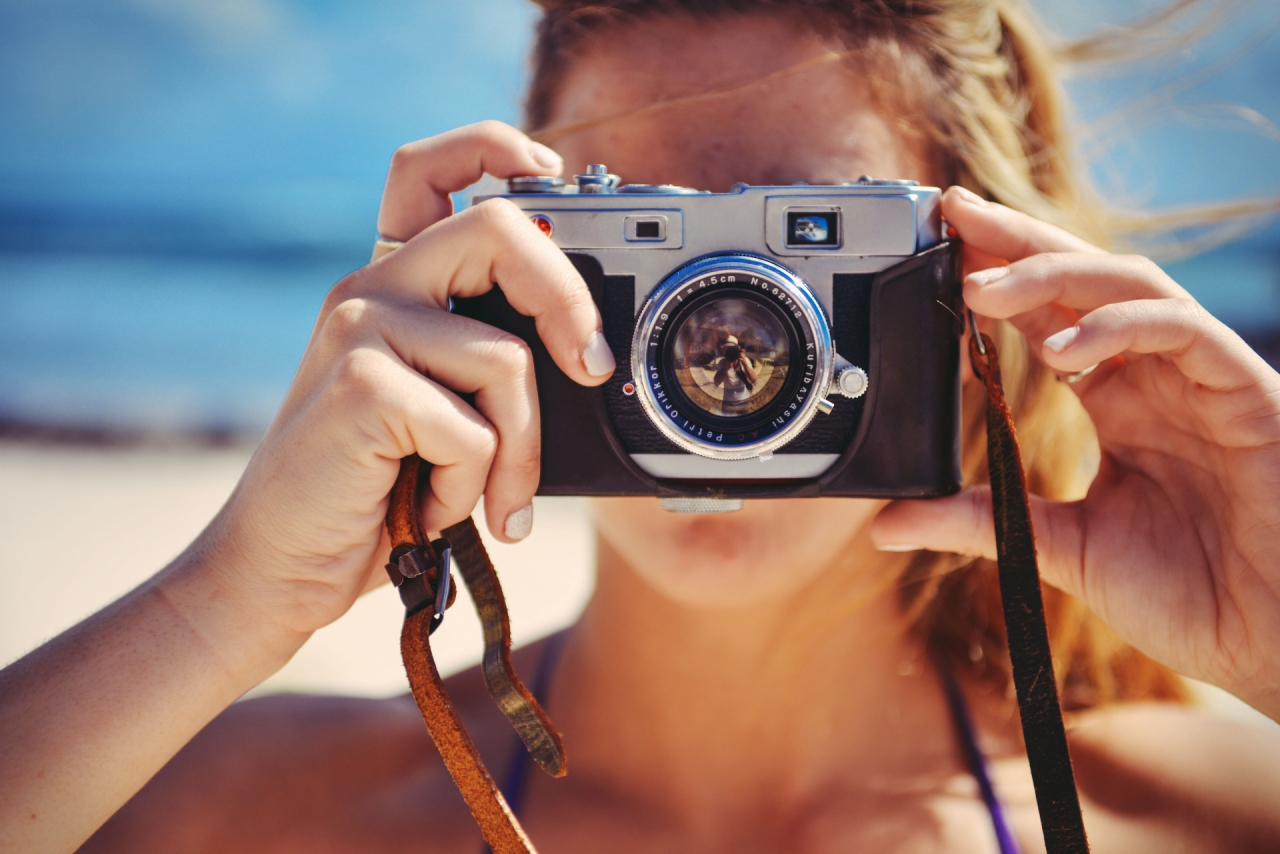 Blond girl holding retro vintage camera, taking a photo during the vacation