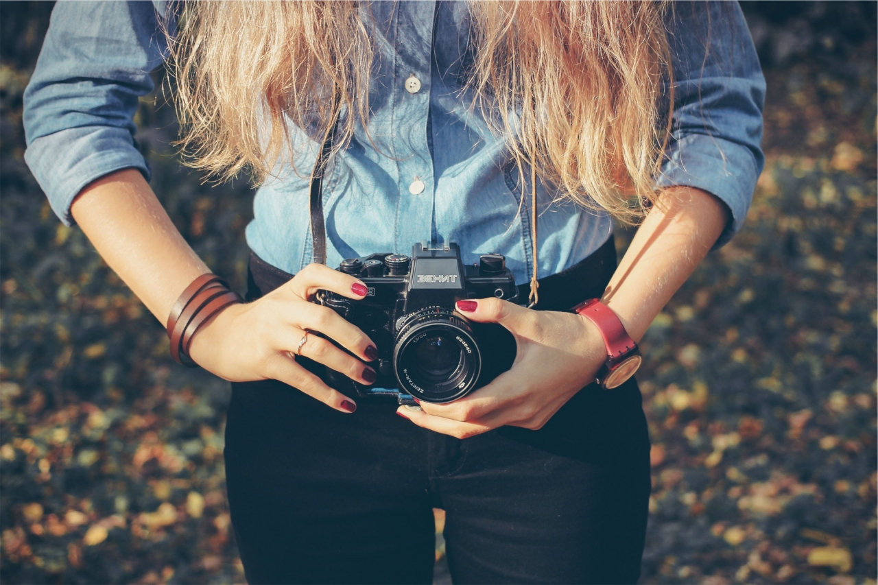 Young blond girl holding a camera